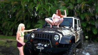 Blonde stepdaughter and red-haired mom are washing the car in jungles